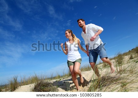 Couple having fun runnning down sand dune - stock photo