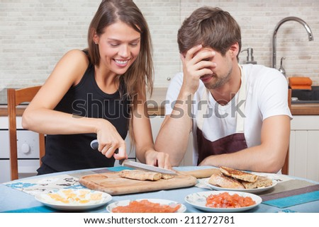 Couple having fun while preparing the dinner together - stock photo