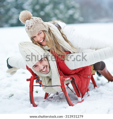 Couple having fun while sledding on sled in winter - stock photo