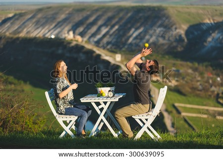 couple having fun with apple at table on hill - stock photo