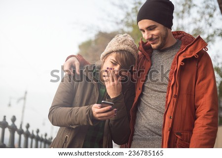 Couple having fun with the smart phone on the streets. - stock photo