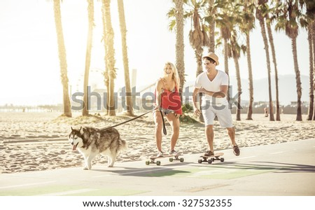 Couple having fun with their Husky dog. the animal pulling while the woman is on the skateboard - stock photo