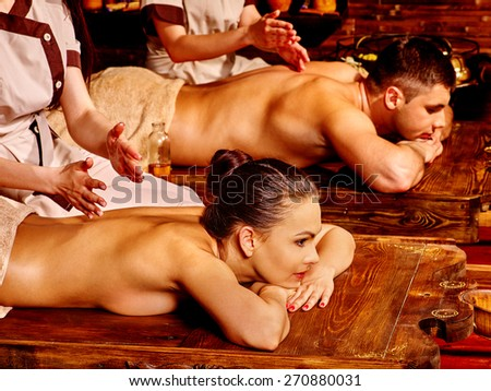 Couple  having oil Ayurveda spa treatment. Wooden bed. - stock photo