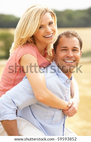 Couple Having Piggyback In Summer Harvested Field - stock photo