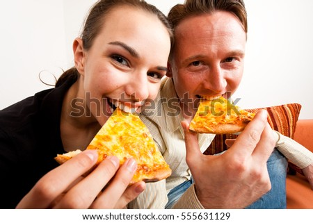 Couple Having Pizza On The Couch