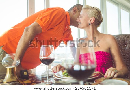 Couple having romantic dinner at restaurant - Man whispers into her woman's ear while having a romantic lunch in a classy restaurant