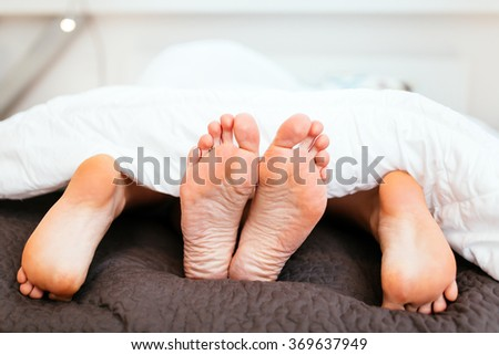 Couple having sex under blanket with their feet visible - stock photo