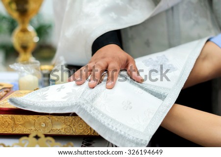 Couple having their wedding ceremony in Orthodox Church. Pastor coveres couple's hands preparing to bless - stock photo