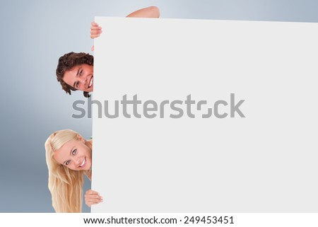 Couple hiding behind a whiteboard against grey vignette - stock photo