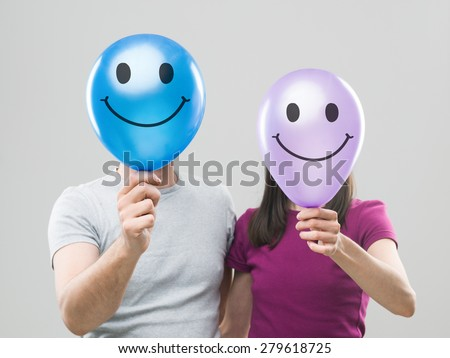 couple hiding their heads behind colorful balloons with smiley faces, against grey background - stock photo