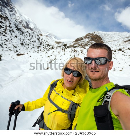 Couple hikers man and woman doing selfie portrait on expedition in winter mountains. Inspiration and motivation. beautiful nature landscape. Fitness lifestyle outdoors on snow in Himalayas, Nepal - stock photo