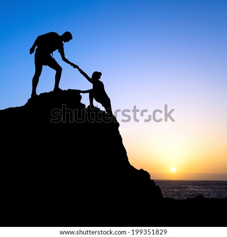 Couple hiking help each other hand teamwork partners climbing silhouette in mountains, achieve adventure. Male and woman hiker helping each other on top of mountain, beautiful sunset landscape. - stock photo