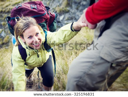 Couple Hiking Helping Climbing Mountain Concept - stock photo
