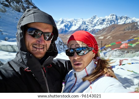 Couple hiking in Himalaya Mountains in Nepal. Man and woman doing self-portrait on Cho La pass 5420 meters. Young people traveling in Asia, trekkers on trail in wilderness. - stock photo