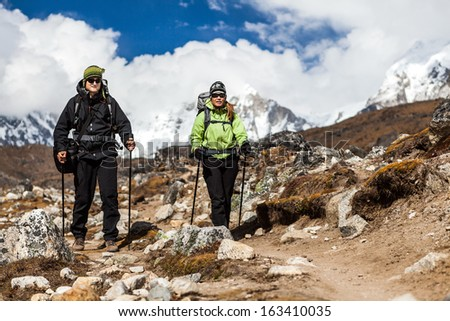 Couple hiking in himalayas mountains in Nepal. Man and woman hikers walking mountain footpath, sunny day traveling. - stock photo