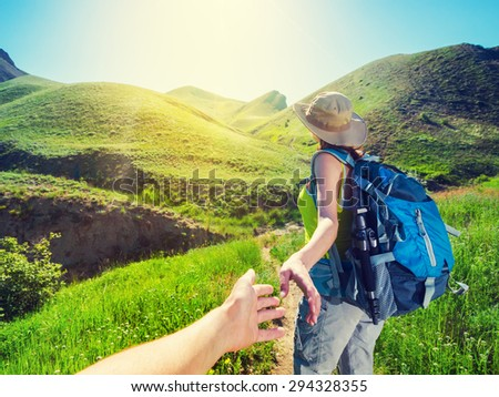 Couple hiking in the mountains. Woman takes hand partner. - stock photo