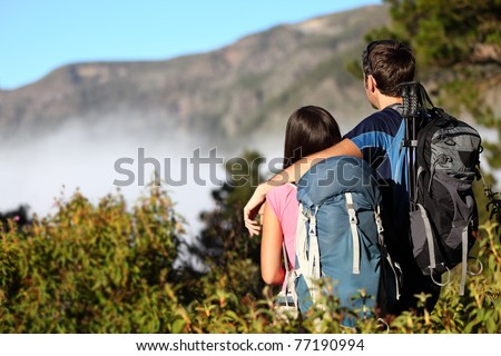 Couple hiking looking at view during hike in forest on Tenerife, Canary Islands, Spain - stock photo