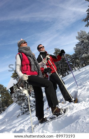 Couple hiking through the snow - stock photo