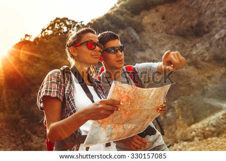 Couple hiking. Using map to get good direction.Sunset. - stock photo