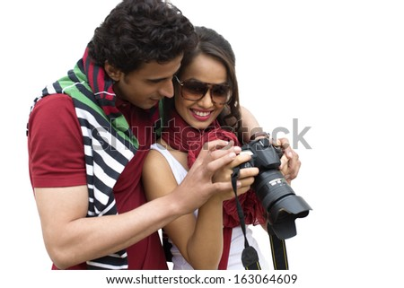 Couple holding a camera and smiling - stock photo