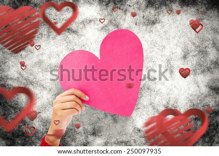 Couple holding a heart against love heart pattern - stock photo