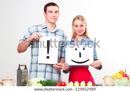couple holding a plate with signs smile and exclamation - stock photo