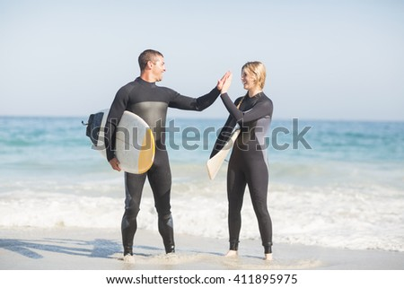 Couple holding a surfboard and giving a high five to each other on the beach - stock photo