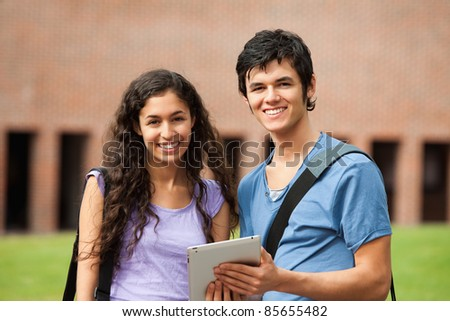 Couple holding a tablet computer outside a building - stock photo