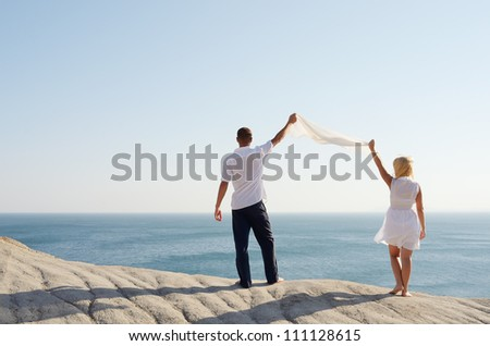 Couple holding a white handkerchief, and looks at the sea