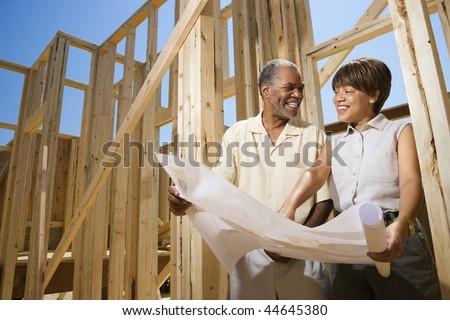 Couple holding blueprints beside construction framing.  Horizontally framed shot. - stock photo