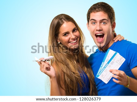 Couple Holding Boarding Pass against a blue background