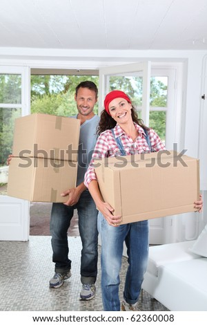 Couple holding boxes in their new home - stock photo