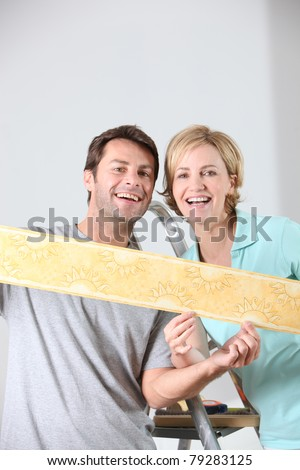Couple holding colorful wallpaper border - stock photo