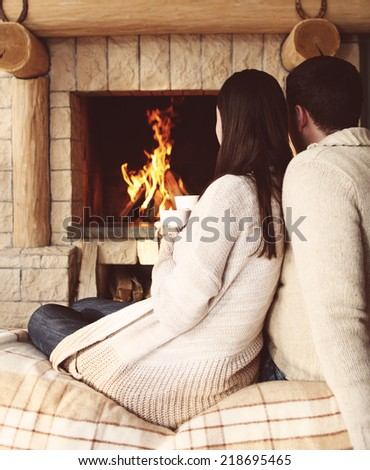 Couple holding cups with hot chocolate with marshmallows in front of lit fireplace - stock photo