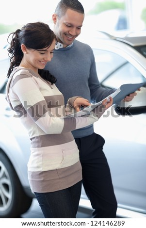 Couple holding documents in a carshop - stock photo
