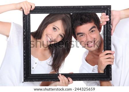 Couple holding empty frame - stock photo