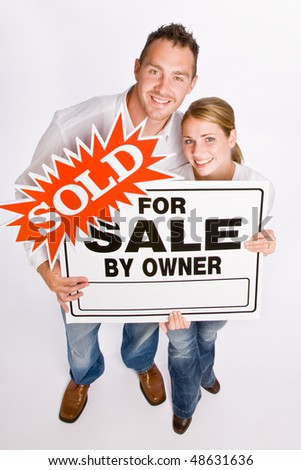 Couple holding for sale sign