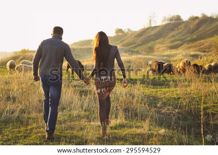 Couple holding hand in hand romantic walk on the autumnal meadow with sheeps - stock photo