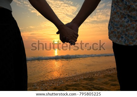Couple holding hands and beautiful sunset on the beach (Had-Sai-Med-Rak) at Phetchaburi province, Thailand.