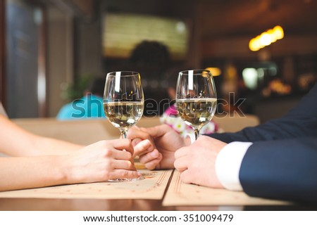 couple holding hands and glasses with wine at cafe