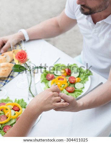 Couple holding hands and resting in the cafe by the sea at the beach. Mature couple in love having a date. - stock photo