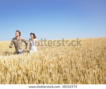 Couple holding hands and running in wheat field - stock photo