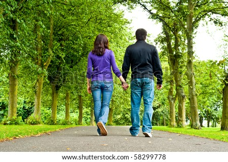 couple holding hands and walking in a park - stock photo