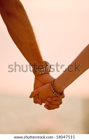 couple holding hands at sunset in a romantic setting - stock photo