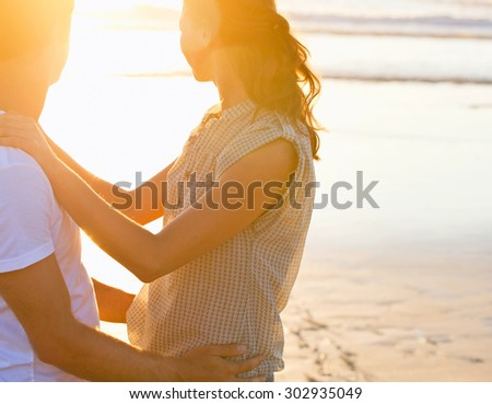 Couple holding hands at sunset on beach - stock photo