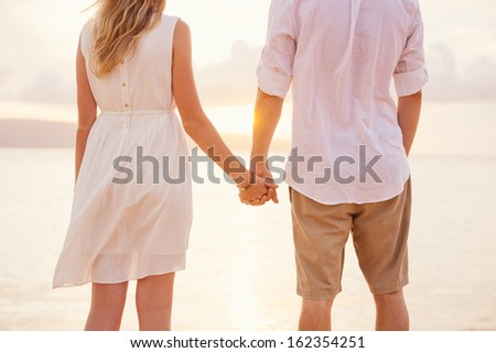 Couple holding hands at sunset on beach. Romantic young couple in love - stock photo