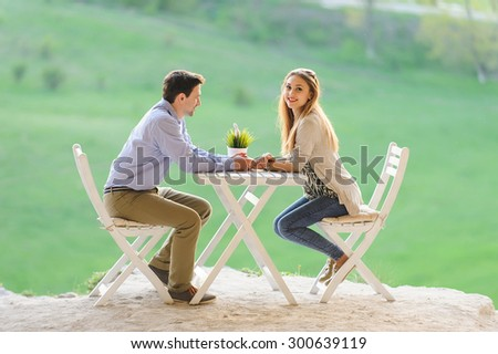 couple holding hands at table - stock photo