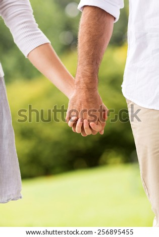 couple holding hands at the park - stock photo