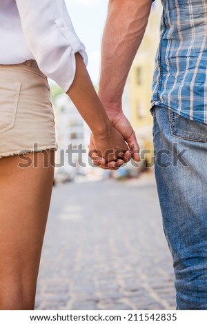 Couple holding hands. Close-up of loving couple holding hands while walking outdoors  - stock photo