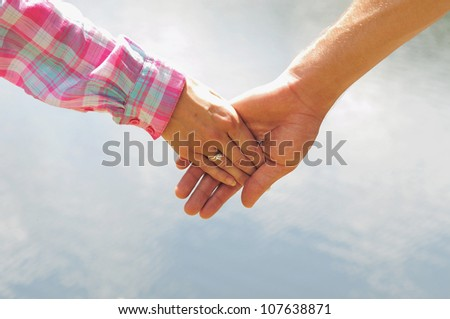 Couple holding hands closeup in nature